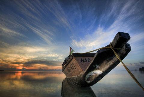 een van twee boomstammen gebouwde boot bij opkomende zon