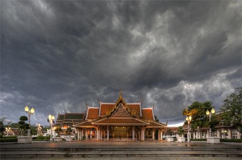 donkere wolken pakken zich samen boven een tempel in Bangkok