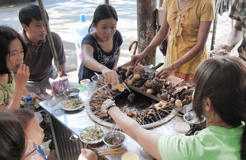 Veel gezien op straat: tafels en krukjes voor mensen die even wat stokjes mee komen eten. Aan de stokjes lekkernijen als pens, long en darm.