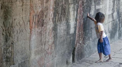 Cambodjaans meisje speelt met muur. Muur speelt mee.