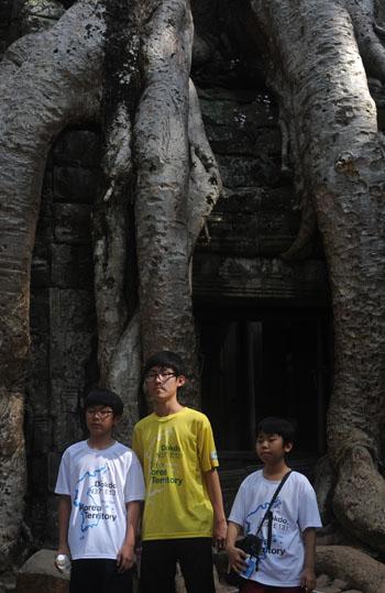 Deze jongens poseren voor een door een enorme boom overwoekerde tempel. Op de foto zijn de wortels van de boom te zien, de stam begint hoger pas. Wat verder opvalt zijn de t-shirts die de jongens dragen; ze maken deel uit van een groep kinderen die allemaal rondlopen met de tekst: Dokdo is Korea territory. Ik heb het opgezocht. Dokdo is de Koreaanse benaming van een aantal vulkanische rotsen die halverweg tussen Korea en Japan uit zee opsteken. In Japan zijn ze bekend onder de naam Takeshima, en de heerschappij over de eilandjes wordt door beide landen opgeëist. Deze kinderen worden dus gebruikt als uithangbord voor misplaatste nationalistische leuzen. Laffe streek. Hele laffe streek. Doet hun zaak geen goed.