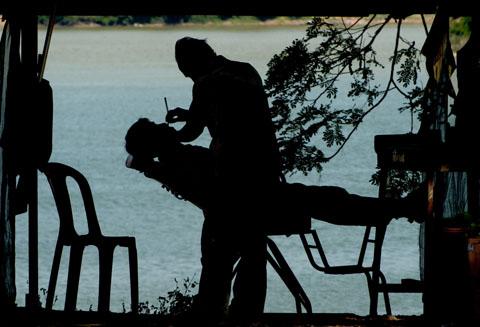 En nog een plaatje van een barbier in Stung Treng, met zicht op de Mekong.