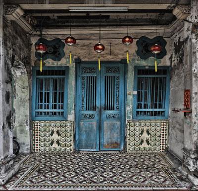 Het enige wat niet typisch is aan deze woning: de ingang is niet volgebouwd met motorfietsen. Maar mede daarom heb ik de foto genomen.