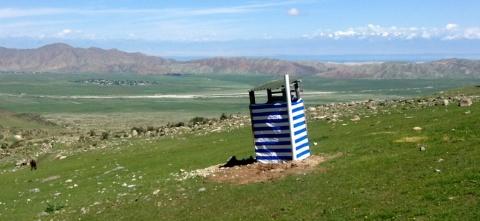 Toilet met uitzicht: achter het dal heuvels, het meer, besneeuwde bergen.