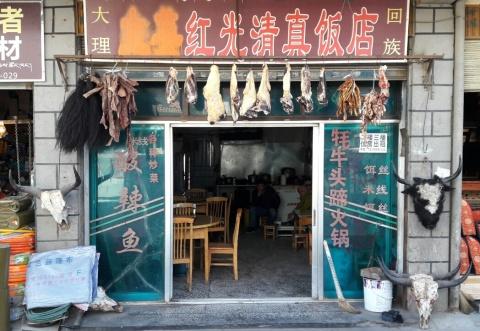Dit hebben we vaker gezien: een eetgelegenheid waar schedels, staarten en allerlei onbeschrijflijkheden bij de ingang hangen. Rechts naast de deuropening valt te lezen wat je er kunt verwachten: jak hoofd hoef 'hot pot'. Hot pot (we kennen het als steamboat in Maleisië en shabu-shabu in Japan, en in het Nederlands als Chinese fondue) bestaat uit een pan bouillon die midden op tafel aan de kook gehouden wordt en waar je zelf allerlei ingrediënten in kookt - in dit geval dus kop en hoeven van de jak.