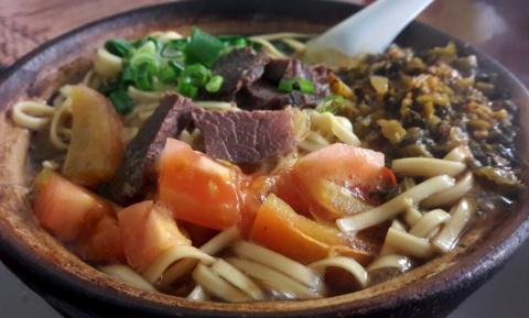 De naam van dit gerecht is te vertalen als 'noedels met jakvlees in aardewerken kom'. Het smaakt nog beter dan het eruit ziet.