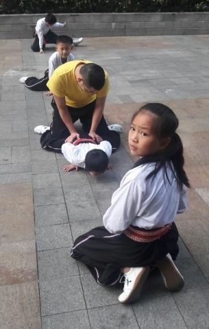 Gewoon op straat, in Guangzhou. Kinderen met kleding waarop tekens staan die 'Shaolin' betekenen worden met ietwat harde hand soepel gemaakt. Niet ieder kind kan daar tegen.